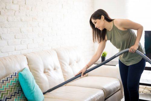 Junge Frau saugt eine Couch mit einem Zentralstaubsauger ab